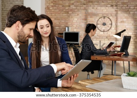 Businesspeople using tablet computer, talking in office.