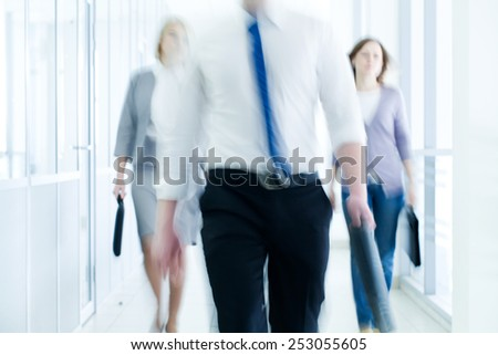 businesspeople walking in the corridor of an business center, pronounced motion blur - stock photo