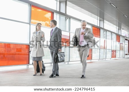 Businesspeople walking while male colleague rushing in railroad station - stock photo