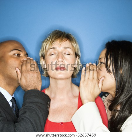 Businesspeople whispering into each ear of businesswoman. - stock photo