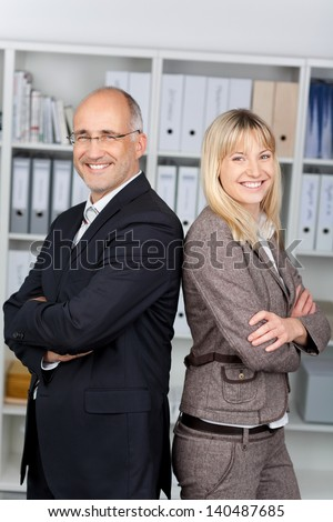 businesspeople with arms crossed standing back to back in office - stock photo