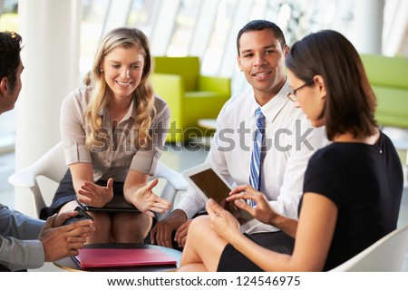 Businesspeople With Digital Tablet Having Meeting In Office - stock photo