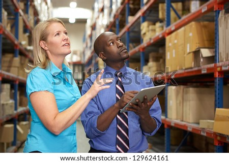 Businesspeople With Digital Tablet In Warehouse - stock photo