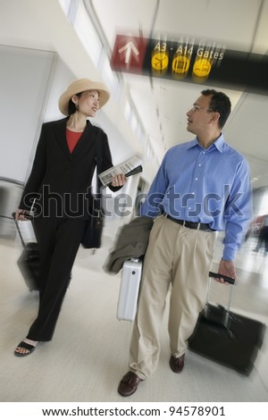 Businesspeople with luggage at airport - stock photo