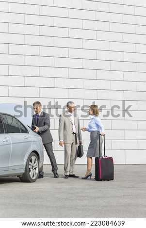 Businesspeople with luggage communicating outside car on street - stock photo