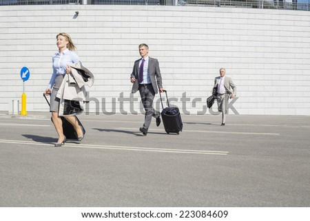 Businesspeople with luggage running on street - stock photo