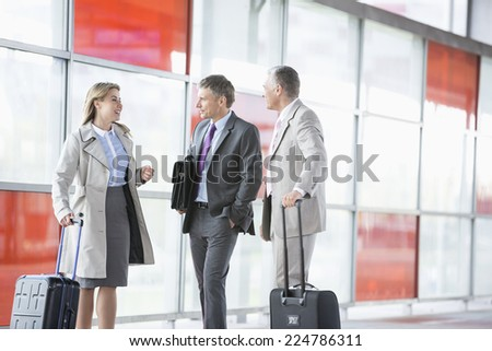 Businesspeople with luggage talking on railroad platform - stock photo
