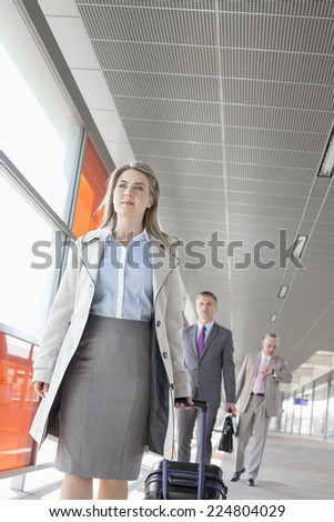Businesspeople with luggage walking on train platform - stock photo