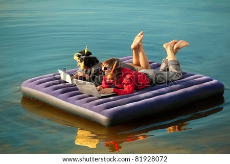 Businesspeople with notebook lieing on inflatable mattress. - stock photo
