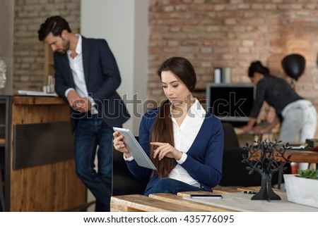 Businesspeople working in busy startup office, using tablet.
