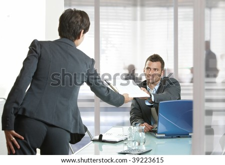 Businesspeople working in office. Smiling businessman handing over documents to businesswoman. - stock photo