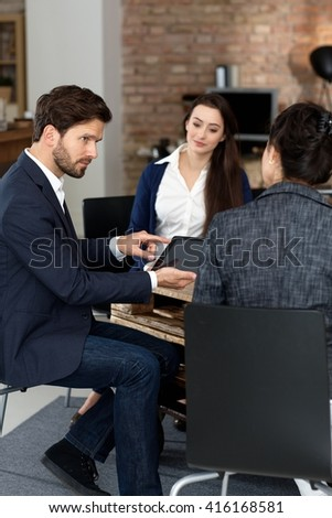 Businesspeople working in startup office, using tablet. - stock photo