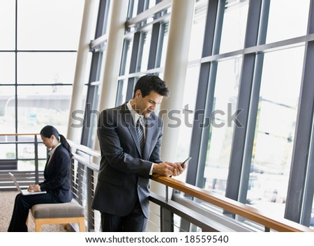 Businesspeople working on laptop and text messaging in office lobby - stock photo