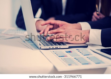 Businesspeople working on laptop. Four smiling successful businessmen sitting at table in office while discussing their business doings. Young people talking in office - stock photo