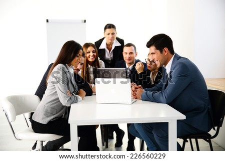 Businesspeople working on laptop in office - stock photo
