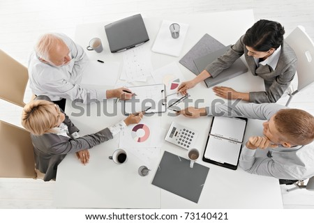 Businesspeople working together at meeting, discussing document on clipboard, high angle view.? - stock photo
