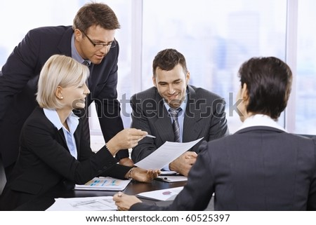 Businesspeople working together at meeting table in office.? - stock photo