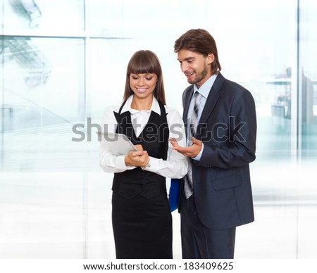 businesspeople working using tablet pad computer, young business man and woman wear elegant suit standing in modern office - stock photo