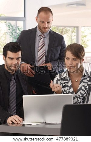 Businesspeople working with laptop computer in office.