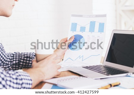 Businessperson analyzing business report and drinking coffee and office desk with laptop - stock photo