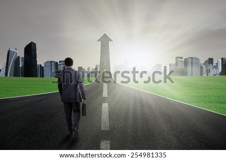 Businessperson carry a briefcase and walk on the road going up as an arrow - stock photo