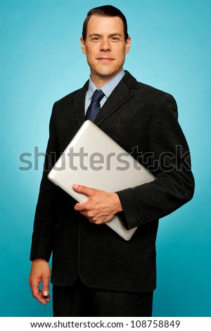 Businessperson carrying a laptop posing against blue background - stock photo