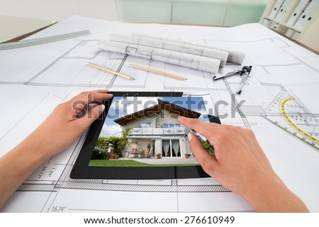 Businessperson Hands With Digital Tablet Over Blueprint In Office. Blueprints were created by photographer - stock photo