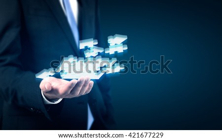 Businessperson holding abstract puzzle pieces on dark background - stock photo