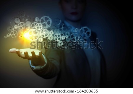 Businessperson holding gears and cogwheels in palm - stock photo