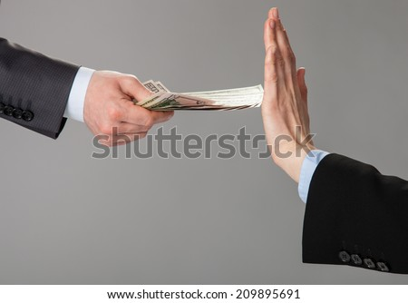 Businessperson's hand rejecting an offer of money on grey background - stock photo