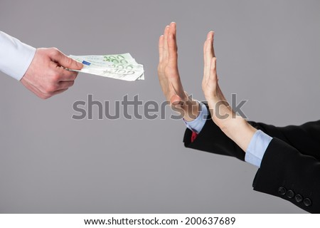 Businessperson's hands rejecting an offer of money on grey background - stock photo