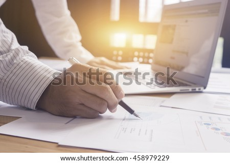 Businessperson Signing Contract, the man writing with pen and reading books at table,Businessman signing of modest agreements Form In office,male hands holding pen, morning light, selective focus. - stock photo