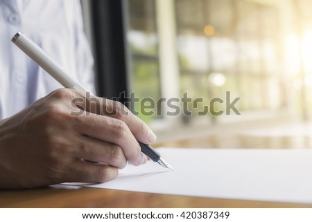 Businessperson Signing Contract,Women writing paper at the desk, man writing with pen and reading books at table,man Signing, Contract, Form. in office ,morning light ,selective focus. - stock photo