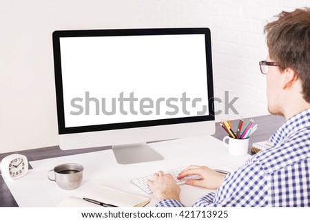 Businessperson typing on keyboard placed on office desk with various items and looking at a blank computer screen. Mock up - stock photo
