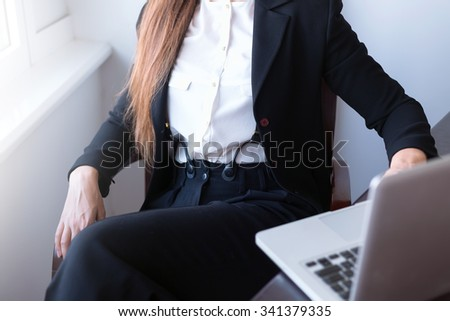 Businessperson using laptop computer.Young pretty business woman with notebook in the office.Young businesswoman sitting at desk and working.Wearing trendy black suit,white blouse and suspenders.  - stock photo