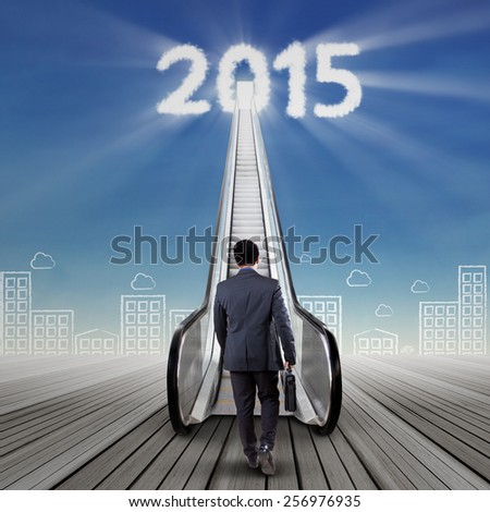 Businessperson with briefcase climbing upward a stair to the future door with numbers 2015 on the sky - stock photo