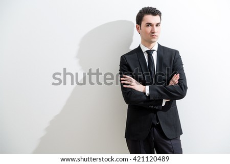 Businessperson with crossed arms standing against white wall with shadow - stock photo