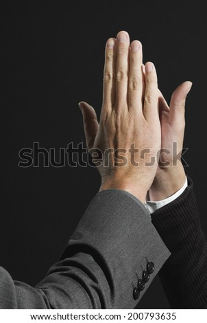Businesspersons giving high five each other - stock photo