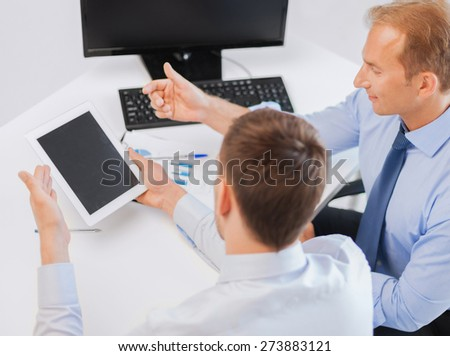businesss and office concept - businessmen with notebook and tablet pc discussing graphs on meeting - stock photo