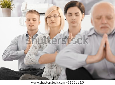 Businessteam doing yoga exercise in office together, sitting on floor with eyes closed.? - stock photo