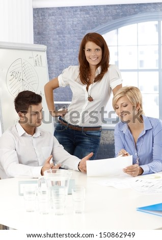Businessteam in meeting room, working on project together, smiling. - stock photo