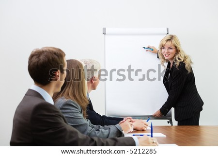 Businessteam listening to a coach giving a presentation on a flip chart (focus on coach) - stock photo