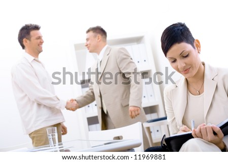 Businessteam of three working at office, businesswoman sitting in foreground, making notes, smiling, businessmen shaking hands in background.