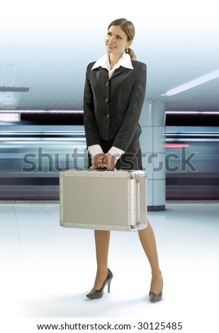 businesstrip of happy young woman with silver suitcase by subway - stock photo