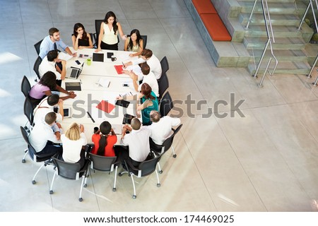 Businesswoman Addressing Meeting Around Boardroom Table - stock photo