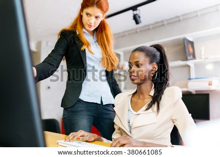 Businesswoman advising colleague in office during work - stock photo