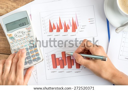 Businesswoman analysing statistical graphs using a manual calculator, view from above of her hands and paperwork on a wooden desk. - stock photo