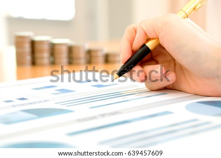 Businesswoman Analyzing Financial Graph With Coins