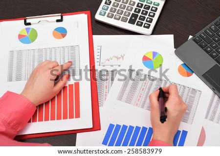 businesswoman analyzing investment charts and calculate income - stock photo