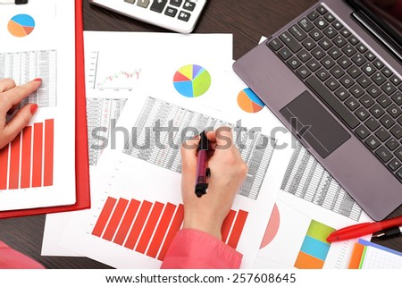 businesswoman analyzing investment charts with laptop - stock photo